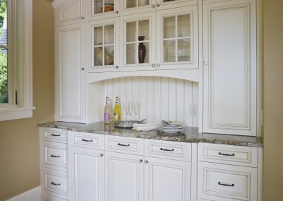 Built in buffet in kitchen has arched inset