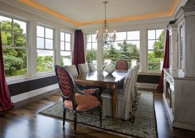 Formal dining room with view of trees and greenery outside
