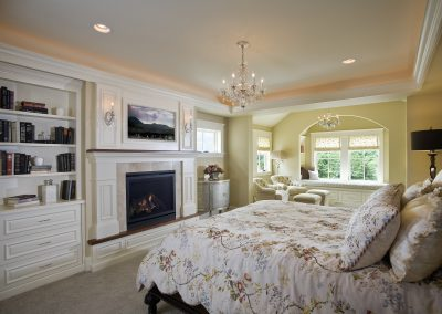 Master bedroom suite with sitting area and television over fireplace mantel