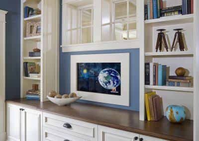 Wall of room showing built in white cabinetry and television