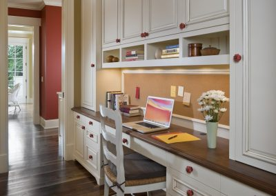Colorful hallway leading into kitchen with built in home office